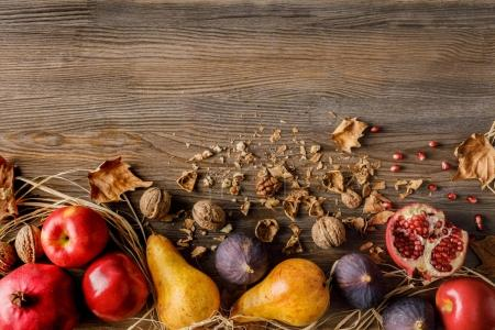 Photo for Top view of pomegranates, pears, apples and walnuts on wooden tabletop - Royalty Free Image