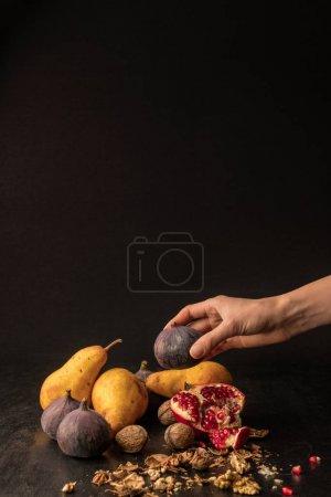 Photo pour Vue recadrée de la main avec des fruits d'automne bio sur table en bois - image libre de droit