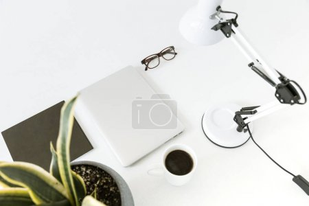 Composition with laptop, desklamp and glasses