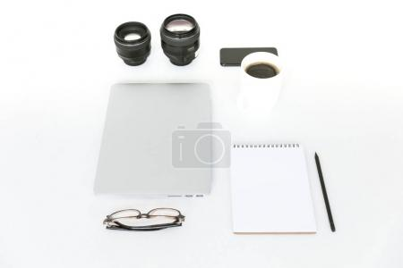 Flat lay with laptop and camera lenses