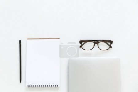 Photo for Top view of composition with laptop, notepad and glasses, isolated on white - Royalty Free Image