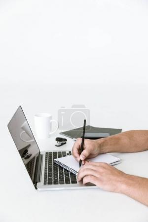 Photo pour Espace de travail minimaliste avec ordinateur portable et mains masculines écrivant dans un ordinateur portable - image libre de droit