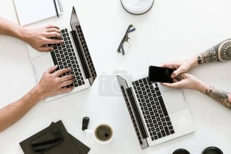 Photo for Top view of workspace with two laptops and male hands typing and using smartphone - Royalty Free Image