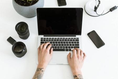 Photo pour Plan recadré d'un homme tapant sur un ordinateur portable placé sur une table blanche avec des lentilles photographiques et un smartphone - image libre de droit