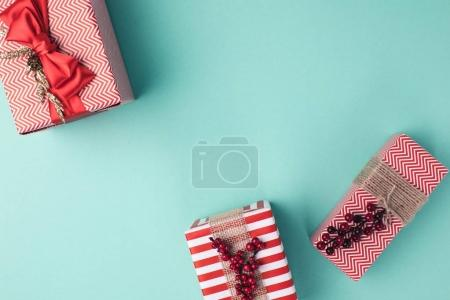 Photo for Top view of arranged christmas gift boxes with ribbons on blue tabletop - Royalty Free Image