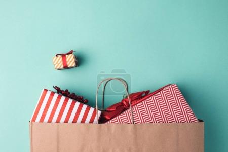 Photo for Top view of wrapped presents in paper bag on blue tabletop - Royalty Free Image