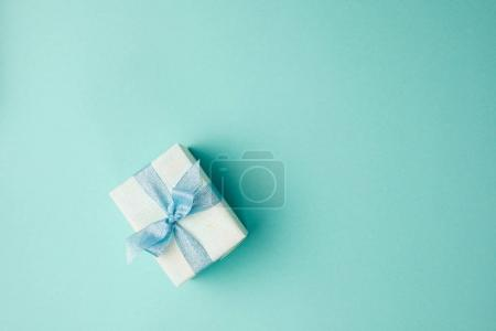 Photo for Top view of festive decorated christmas gift with ribbon on blue surface - Royalty Free Image