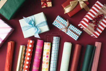 Photo for Flat lay with arranged colorful  christmas presents and wrapping papers on tabletop - Royalty Free Image