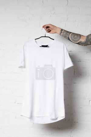 Photo for Cropped shot of man holding hanger with blank white t-shirt - Royalty Free Image