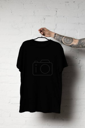 Photo for Cropped shot of man holding hanger with blank black t-shirt - Royalty Free Image