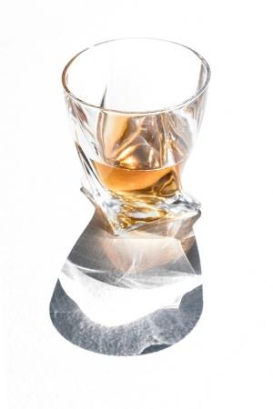 Photo for Close-up view of whiskey in glass with shadow on white - Royalty Free Image
