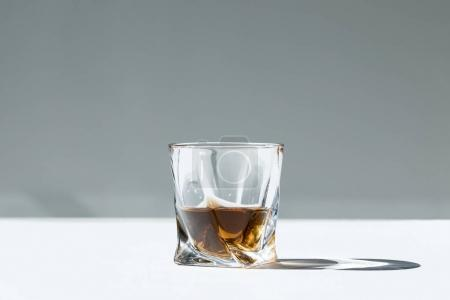 Photo for Close-up view of whiskey in glass on grey - Royalty Free Image