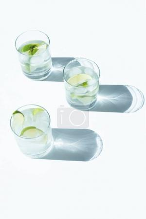 Foto de Vista cercana de Gin Tonic cóctel con limón y cubitos de hielo en vasos y las sombras en blanco - Imagen libre de derechos