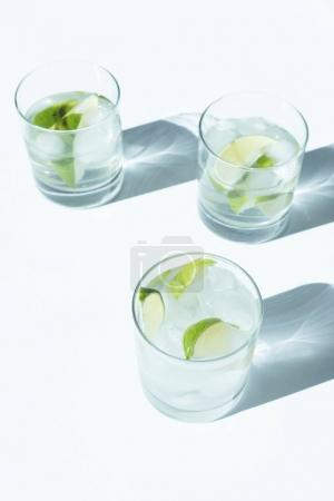 Photo for Close-up view of Gin Tonic cocktail with lime and ice cubes in glasses on white - Royalty Free Image
