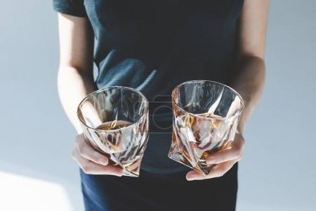 Photo for Close-up partial view of person holding glasses with luxury brandy - Royalty Free Image