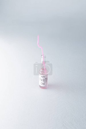 Photo for Alcoholic beverage in bottle with drinking straw and inscription isolated on grey - Royalty Free Image