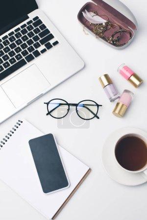 Photo pour Travail girly moderne avec ordinateur portable et d'élégantes lunettes - image libre de droit