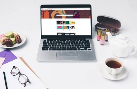 Photo for Laptop with shutterstock website at modern girly workplace - Royalty Free Image