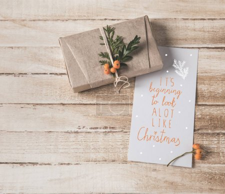 Photo for Christmas card with greeting and present with rowan decoration on shabby wooden tabletop - Royalty Free Image
