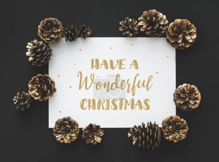 Photo for Frame of pine cones and card with Christmas greeting - Royalty Free Image