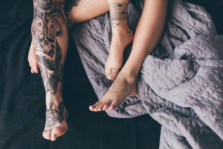 tattooed couple in bed