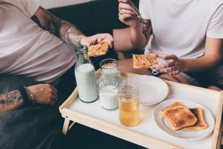 Pareja desayunando juntos en la cama