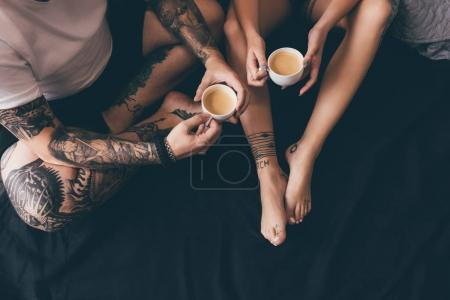 Photo for Overhead view of tattooed couple with cups of aromatic coffee in bed - Royalty Free Image