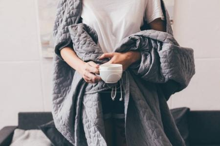 woman in blanket with cup of coffee