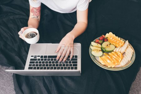 Photo for Cropped shot of woman using laptop while resting on bed with healthy breakfast at home - Royalty Free Image
