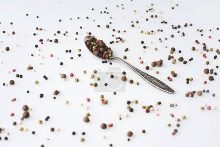 spoon with spilled peppercorns