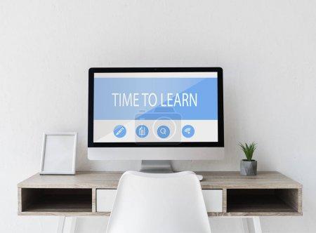 Photo pour Ordinateur avec thème d'apprentissage à l'écran sur la table avec pot de fleurs - image libre de droit