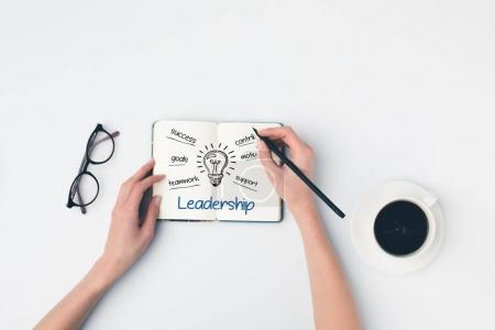 writing leadership ideas in notebook