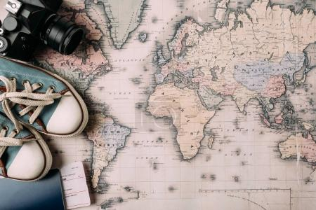 Photo for Top view of film camera with gumshoes and passport on a map. trip concept - Royalty Free Image