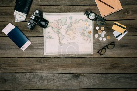 Photo for Top view of map, money, film camera, passport with a ticket on a wooden surface - Royalty Free Image