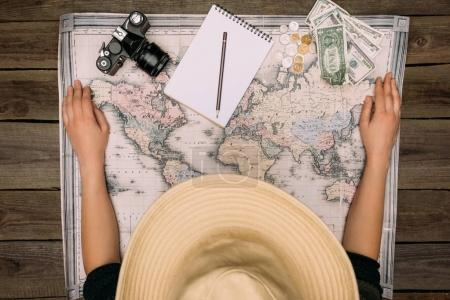 Photo for Top view of woman in a beige hat sitting and looking at map on a wooden table, travel concept - Royalty Free Image