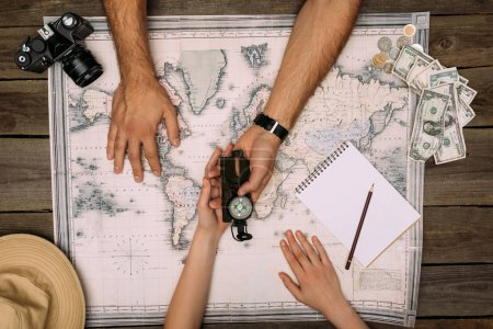 couple planning travel and looking at compass