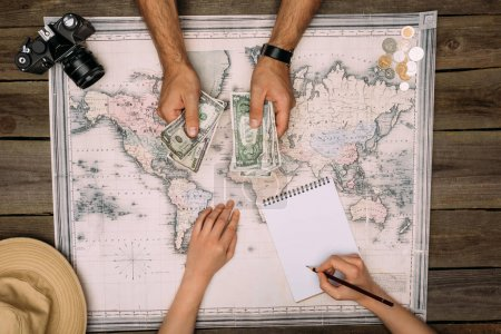 Photo for Couple of tourists planning a travel and counting money on a map - Royalty Free Image