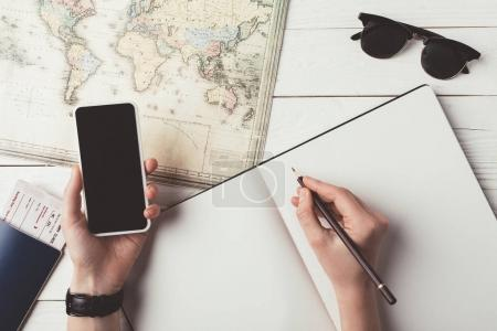 man planning travel with smartphone and map