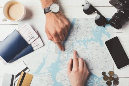 Photo for Couple of travelers showing something on a map at the table - Royalty Free Image