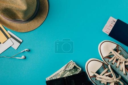 Photo for Money and credit cards with hat and gumshoes on a turquoise - Royalty Free Image