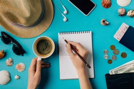 Woman planning travel with notebook and pencil