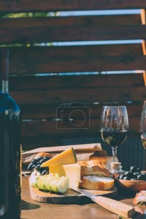 Photo for Wooden board with delicious snacks for red wine - Royalty Free Image