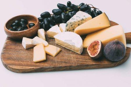 Photo pour Diverses collations pour le vin sur une planche à découper en bois isolé sur blanc - image libre de droit