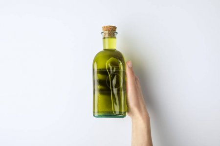 woman holding bottle of olive oil