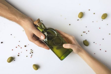 man and woman holding bottle of oil