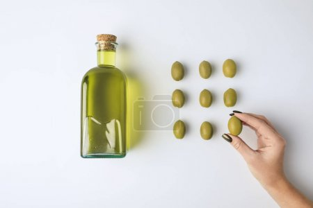 oil bottle and woman holding olive
