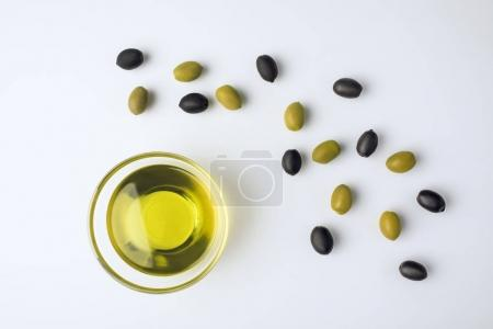 Photo for Top view of glass bowl with olive oil and scattered green and black olives isolated on white - Royalty Free Image