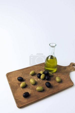 Bottle of olive oil and olives on board