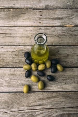 Photo pour Bouteille en verre avec l'huile d'olive et les olives sur une table en bois grungy - image libre de droit