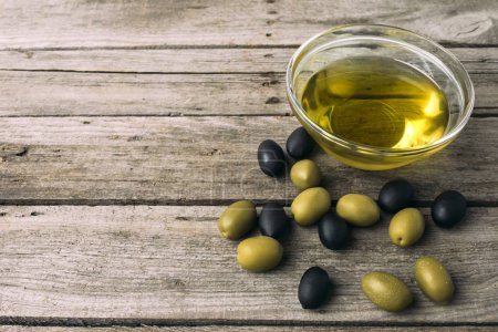 Photo for Glass bowl with olive oil and olives on a wooden grungy tabletop - Royalty Free Image